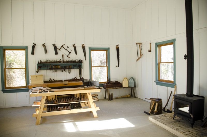 Interior of Joshua Farnsworth's Wood And Shop Traditional Woodworking School with workbenches, woodworking hand tools, and wood stove