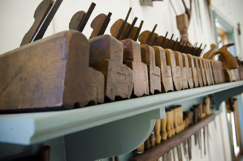 Antique moulding planes (molding planes) lined up on a shelf in Joshua Farnsworth's Wood And Shop Traditional Woodworking School