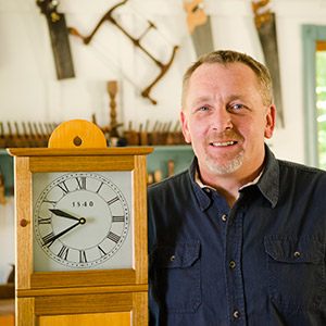 Will Myers woodworking instructor at the woodandshop traditional woodworking school with a Isaac Youngs reproduction shaker wall clock