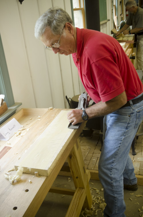 male woodworking student using a stanley bailey No. 7 jointer plane to flatten the face of a poplar board on a woodworking workbench at Joshua Farnsworth's Wood And Shop Woodworking School