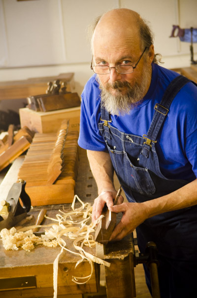 Bill Anderson using a molding plane on a woodworking workbench with hollows and rounds planes in the backgorund