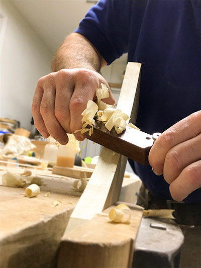 Tom Calisto using a wooden spokeshave that he makes in a woodworking class